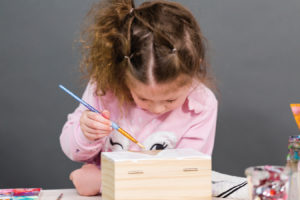 Child decorating a box