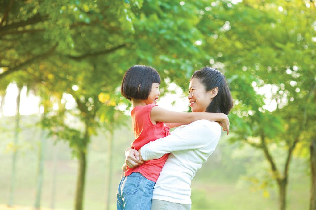 Adult hugging child