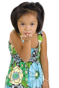 child blowing a kiss