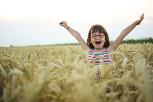 Child with arms raised in sunshine