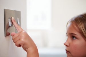 Child turning on light switch